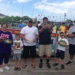 Family of six holding fish next to an Ocean city fishing boat