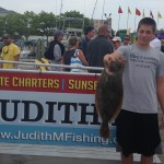 Teenage boy in grey shirt caught brown flounder on Judith M fishing boat