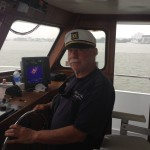 Older man wearing captain hat and steering Judith M fishing boat