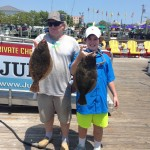 Older man and young boy holding two brown flounder in Ocean City Maryland