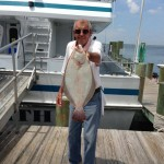 Older man standing on Ocean city fishing dock with flounder