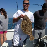 Man wearing sunglasses with flounder aboard the Judith M charter boat