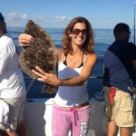 A woman displaying a brown flounder on the Judith M charter boat