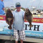 Man next to Judith M charter boat holding two flounder